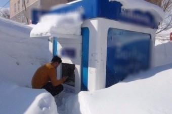 Bitlis'te kar kalınlığı nedeniyle birçok mahalle ve anayollar adeta tünel haline gelirken, karla kaplanan ATM'nin önünde para çekmeye çalışan bir vatandaş ilginç görüntü oluşturdu.  Fotoğraf: Vahit Olcay