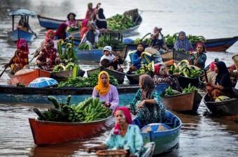 Endonezya'nın Güney Kalimantan bölgesinde bulunan Lok Baintan nehrinde, çoğunluğu kadınlardan oluşan satıcılar, kanolarla hasat aldıkları sebze ve meyveleri satıyor.