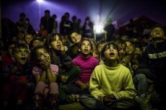 Daha iyi bir yaşam umuduyla Batı Avrupa ülkelerine ulaşmanın hayalini kuran sığınmacıların geldiği Yunanistan'ın Makedonya sınırındaki İdomeni kasabasında bulunan kampta çocuklar için film izleme etkinliği düzenlendi.