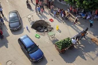 Adana'da şiddetli yağmurun ardından yol ortasında oluşan çukura yayaların ve araçların düşmemesi için vatandaşlar belediye ekipleri gelene kadar simit aracı ve meyve-sebze kasalarıyla önlem aldı.  Fotoğraf: Fatih Keç